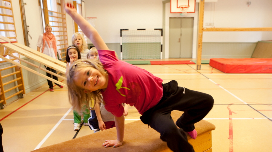 A girl jumping a box in gymclass.